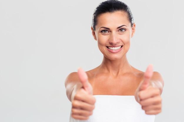 Szczęśliwa piękna kobieta w ręcznik pokazując kciuk do góry znak na białym tle na białym tle. patrząc na aparat