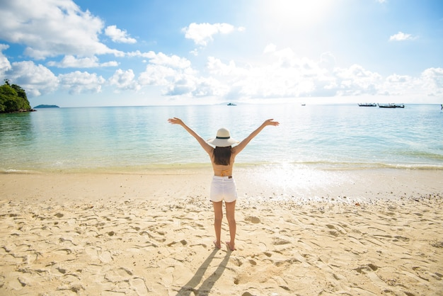 Szczęśliwa piękna kobieta w żółtym bikini ciesząca się i relaksująca na plaży