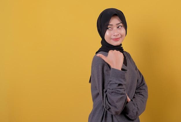Szczęśliwa piękna kobieta wskazując kciukiem na sobie przypadkową koszulkę i czarną zasłonę