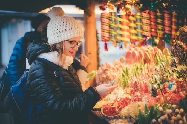Szczęśliwa piękna kobieta wybiera tradycyjnych wakacyjnych cukierki