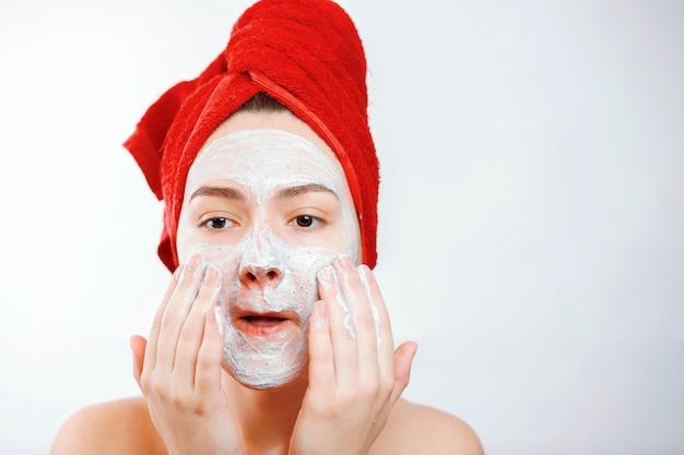 Szczęśliwa piękna kobieta z czerwonym ręcznikiem na głowie nakłada peeling na twarz dużego portretu na białej ścianie emocjonalnej roli płciowej
