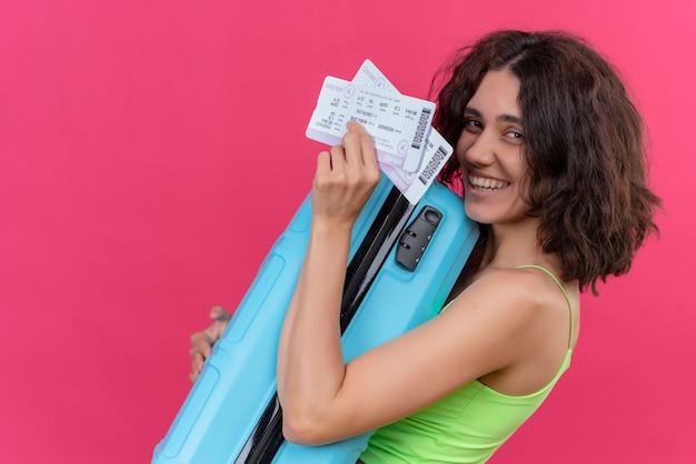 Szczęśliwa piękna kobieta z krótkimi włosami, ubrana w zielony krótki top pokazujący bilet lotniczy z niebieską walizką