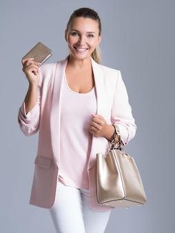 Szczęśliwa piękna kobieta z torebką i portfelem w zakupach