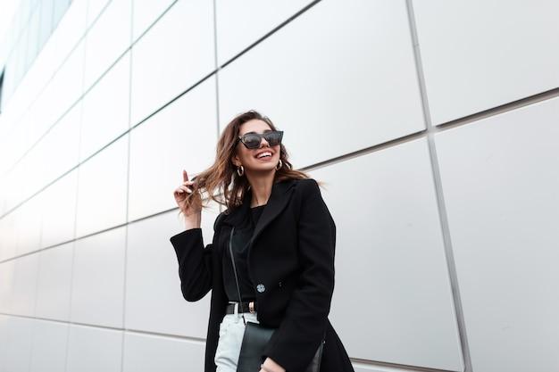 Szczęśliwa piękna kobieta z uśmiechem w moda czarne ubrania