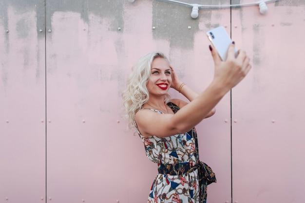 Szczęśliwa piękna kobieta z uśmiechem w sukience vintage robi selfie na smartfonie w pobliżu różowej ściany na ulicy