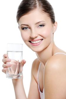 Szczęśliwa piękna kobieta ze zdrowymi białymi zębami trzymając szklankę czystej wody