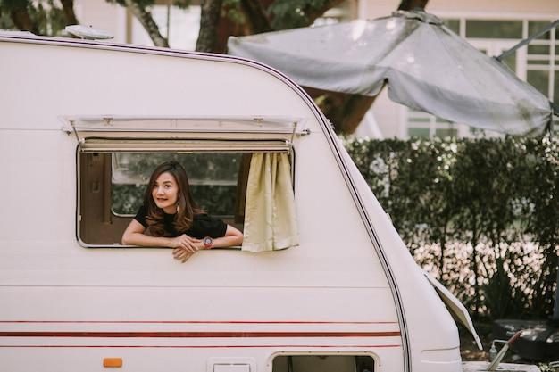 Szczęśliwa piękna ładna azjatycka kobieta przy oknie samochodu kempingowego