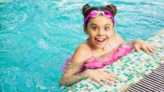 Szczęśliwa piękna mała uśmiechnięta dziewczyna w okularach i stroju kąpielowym w basenie dobrze się bawi podczas wakacji lub lekcji pływania.