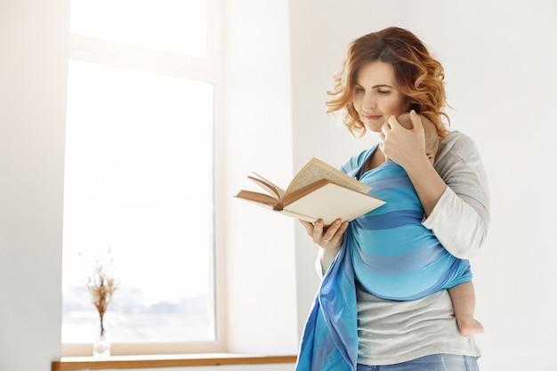 Szczęśliwa piękna matka przytula swoje drzemiące dziecko do piersi i czyta książkę o edukacji dziecka w jasnym, przytulnym pokoju przed oknem. rodzinne chwile.