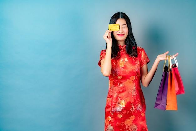 Szczęśliwa piękna młoda azjatycka kobieta nosi czerwony chiński tradycyjny strój z ręką trzymającą kartę kredytową i torby na zakupy