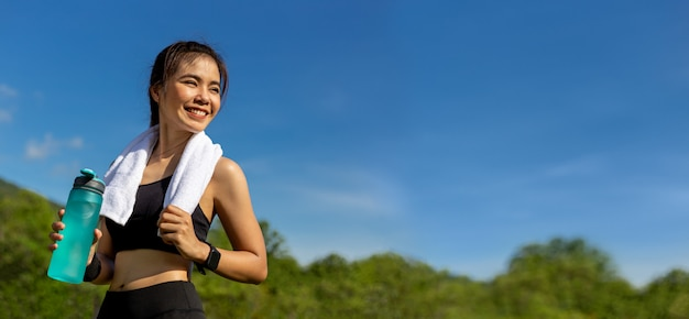 Szczęśliwa piękna młoda azjatycka kobieta z białym ręcznikiem na szyi, stojący uśmiechnięty i trzymający butelkę wody do picia po porannym ćwiczeniu w parku