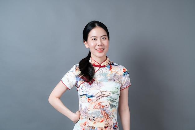 Szczęśliwa piękna młoda azjatykcia kobieta nosi chiński tradycyjny strój na szarej ścianie