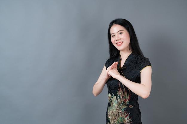 Szczęśliwa piękna młoda azjatykcia kobieta nosi czarną chińską tradycyjną sukienkę na szarej ścianie