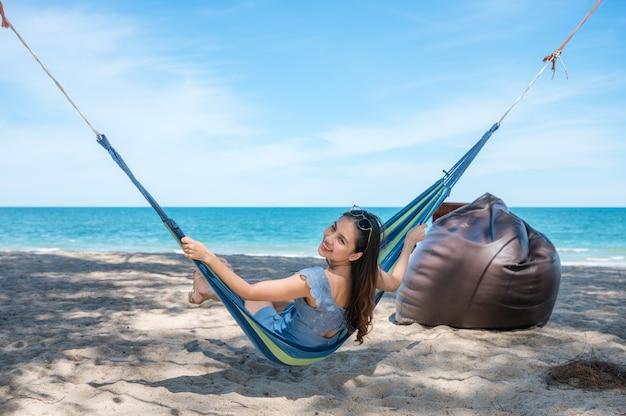 Szczęśliwa piękna młoda azjatykcia kobieta siedzi na hamaku na plaży na wakacjach