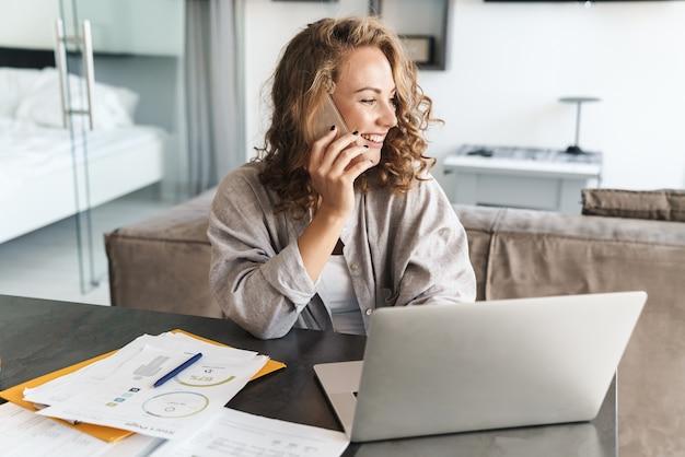 Szczęśliwa piękna młoda blond włosa kobieta siedzi przy stole w domu, pracując na laptopie, rozmawiając przez telefon komórkowy