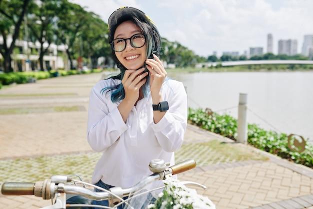 Szczęśliwa piękna młoda chinka z niebieskimi włosami, zakładając kask przed jazdą na rowerze wokół miejskiego stawu