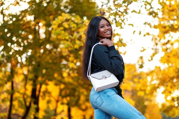 Szczęśliwa piękna młoda czarna dziewczyna z uśmiechem w modnej kurtce i stylowych niebieskich dżinsach z białą skórzaną torebką w kanadyjskim parku z jasnożółtymi jesiennymi liśćmi klonu
