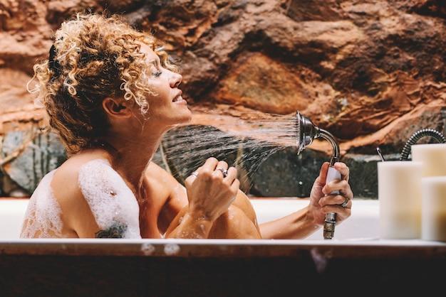 Szczęśliwa piękna młoda dorosła kobieta mycie z prysznicem, siedząc w łazience w domu. pielęgnacja ciała i uroda zmieniają styl życia kobiety cieszą się mydłem i wodą w kąpieli