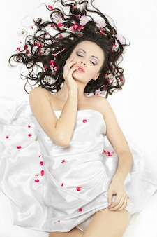 Szczęśliwa piękna młoda dziewczyna brunetka pokryta prześcieradłem w jasne kwiaty na białym tle