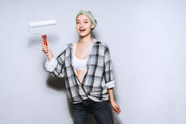 Szczęśliwa piękna młoda dziewczyna malarz robi naprawy, maluje ściany za pomocą wałka