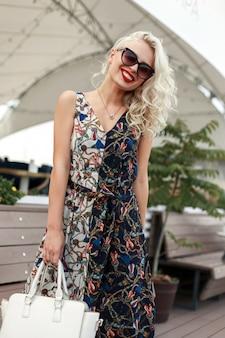 Szczęśliwa piękna młoda dziewczyna ze stylowymi okularami przeciwsłonecznymi w sukienka vintage z torbą na ulicy