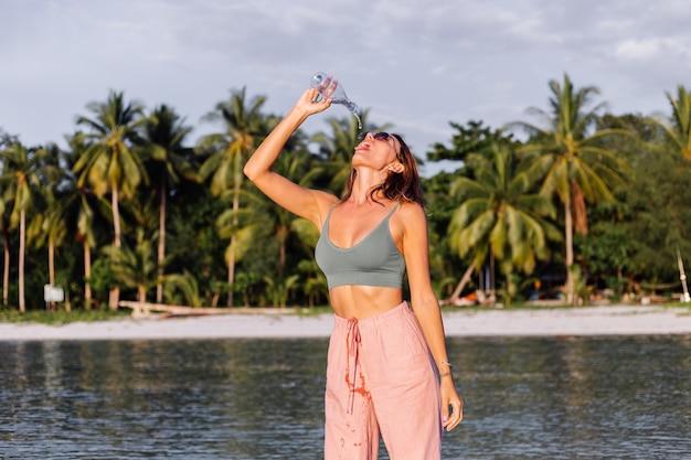 Szczęśliwa piękna młoda europejska kobieta z plastikową butelką wody w dłoni na plaży