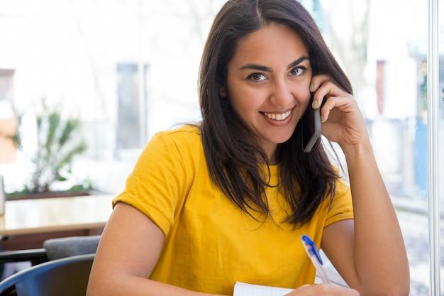 Szczęśliwa piękna młoda kobieta opowiada na smartphone