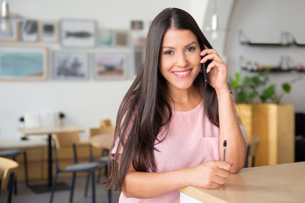 Szczęśliwa piękna młoda kobieta rozmawia przez telefon komórkowy, stojąc w coworkingu, opierając się na biurku,