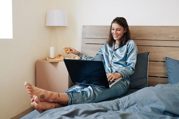 Szczęśliwa piękna młoda kobieta spędza weekend w domu, jedząc rogaliki i oglądając serie na laptopie