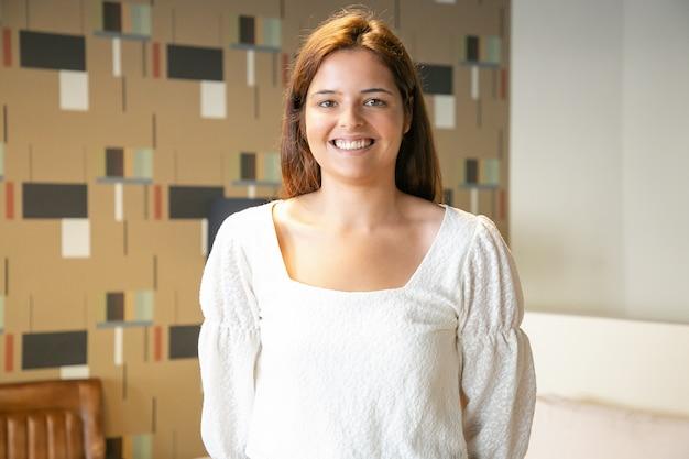 Szczęśliwa piękna młoda kobieta stojąc i pozowanie we wnętrzu co-working lub kawiarnia, patrząc na kamery i uśmiechnięty