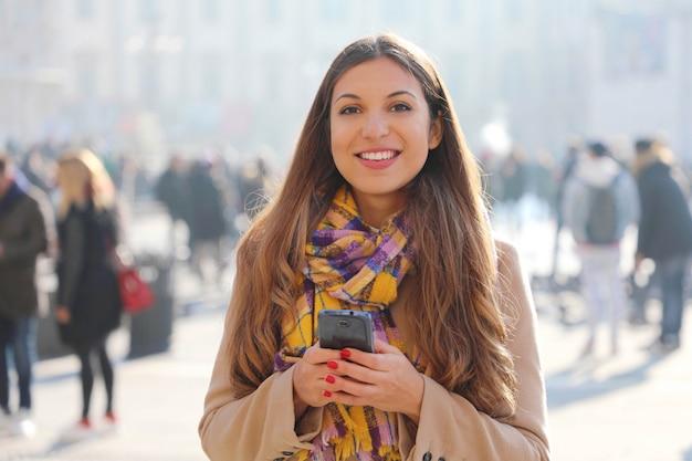 Szczęśliwa piękna młoda kobieta szuka i trzyma telefon komórkowy odkryty z niewyraźne tłum ludzi na ulicy
