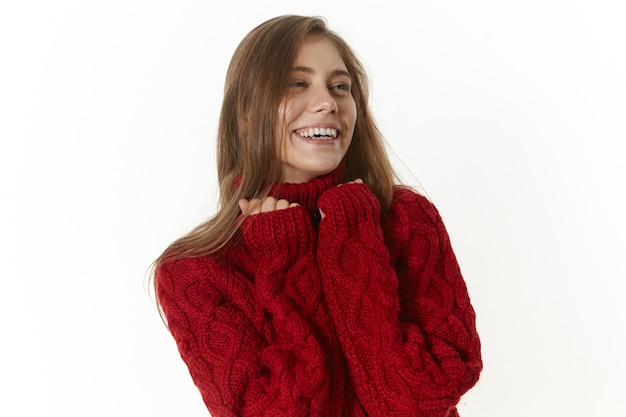 Szczęśliwa piękna młoda kobieta ubrana w bordowy sweter z długimi rękawami, smilijg radośnie. pozytywna, przyjazna dziewczyna z czarującym szerokim uśmiechem, pozująca w pomieszczeniu w stylowym swetrze z dzianiny