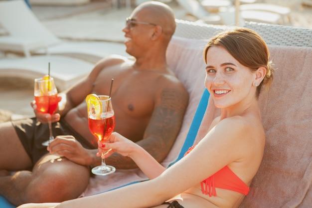 Szczęśliwa piękna młoda kobieta w bikini symulującym kamerę, jej przystojny chłopak opalający się w tle. wieloetniczna para relaksuje na plaży