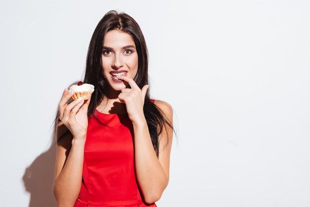 Szczęśliwa piękna młoda kobieta w czerwonej sukience trzyma ciastko