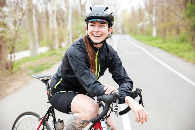 Szczęśliwa piękna młoda kobieta w kasku rowerowym na rowerze stojącym na drodze i śmiejąca się