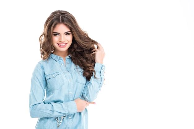 Szczęśliwa piękna młoda kobieta w niebieskiej koszuli dżinsowej bawi się włosami na białej ścianie
