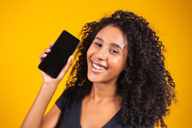 Szczęśliwa piękna młoda kobieta z afro włosami trzymająca pusty ekran telefonu komórkowego na żółtym tle uśmiecha się do kamery