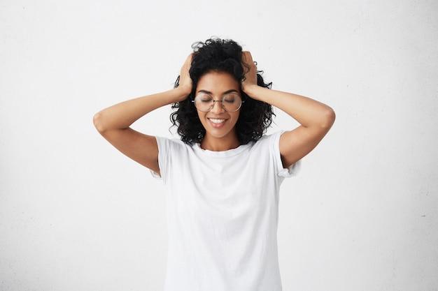 Szczęśliwa piękna młoda kobieta z ciemną skórą, dotykając jej czarne włosy