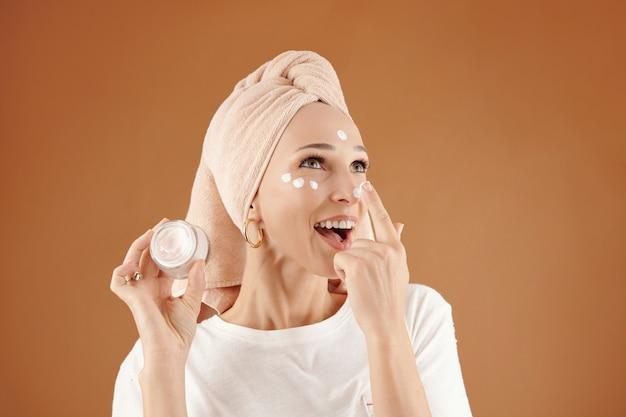 Szczęśliwa piękna młoda kobieta z ręcznikiem na włosach, stojąca na brązowym tle i nakładająca krem na nos, trzymając słoik z kremem