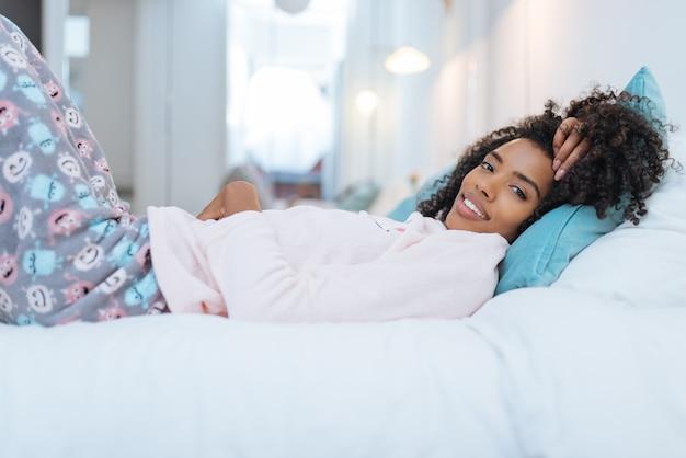 Szczęśliwa piękna młoda murzynka relaksował łgarskiego puszek w łóżku