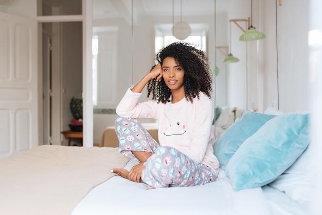 Szczęśliwa piękna młoda murzynka relaksował obsiadanie w łóżku
