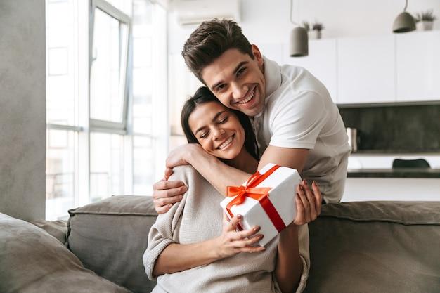 Szczęśliwa piękna młoda para świętuje razem, siedząc na kanapie w domu