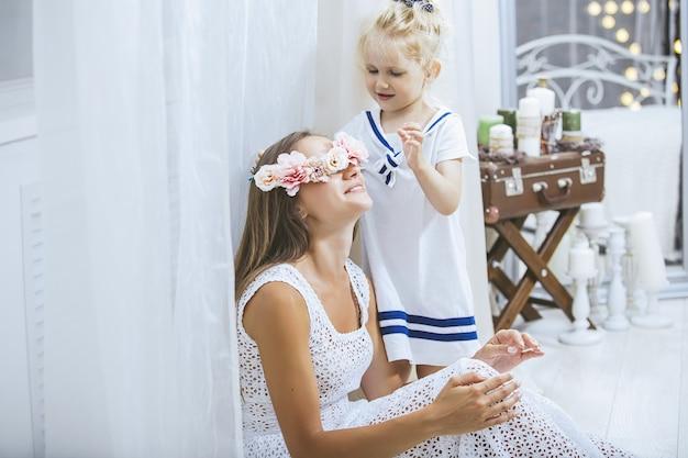 Szczęśliwa piękna młoda rodzina matka i córka uśmiechają się i bawią się w dom z kwiatami