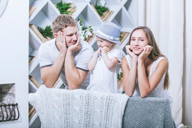 Szczęśliwa piękna młoda rodzina moda ojciec, matka i córka, uśmiechając się razem w domu