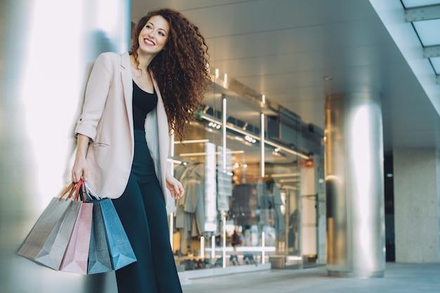 Szczęśliwa piękna młoda rudzielec kobieta robi zakupy