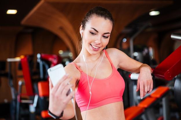 Szczęśliwa piękna młoda sportsmenka słuchania muzyki i robienia selfie ze smartfonem w siłowni
