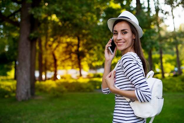 Szczęśliwa piękna młoda studencka kobieta w kapeluszu z inteligentny telefon i plecak podczas spacerów na świeżym powietrzu w parku