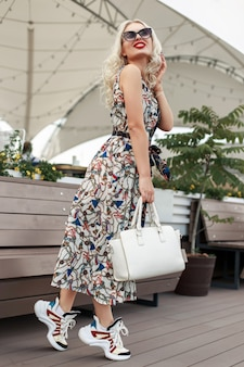 Szczęśliwa piękna modelka w modnej sukience vintage z wzorem z okularami przeciwsłonecznymi i stylowymi butami w mieście