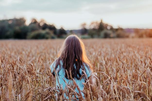 Szczęśliwa piękna nastolatka dziewczyna z długimi włosami na polu pszenicy w czasie zachodu słońca