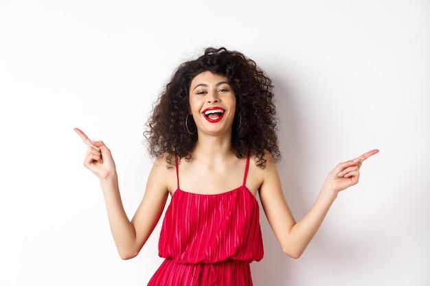 Szczęśliwa piękna pani w czerwonej sukience, śmiejąc się i wskazując bokiem, pokazując dwa sposoby, stojąc na białym tle.